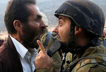 Palestinian man argues with an Israeli soldier during clashes over an Israeli order to shut down a Palestinian school near Nablus in the occupied West Bank