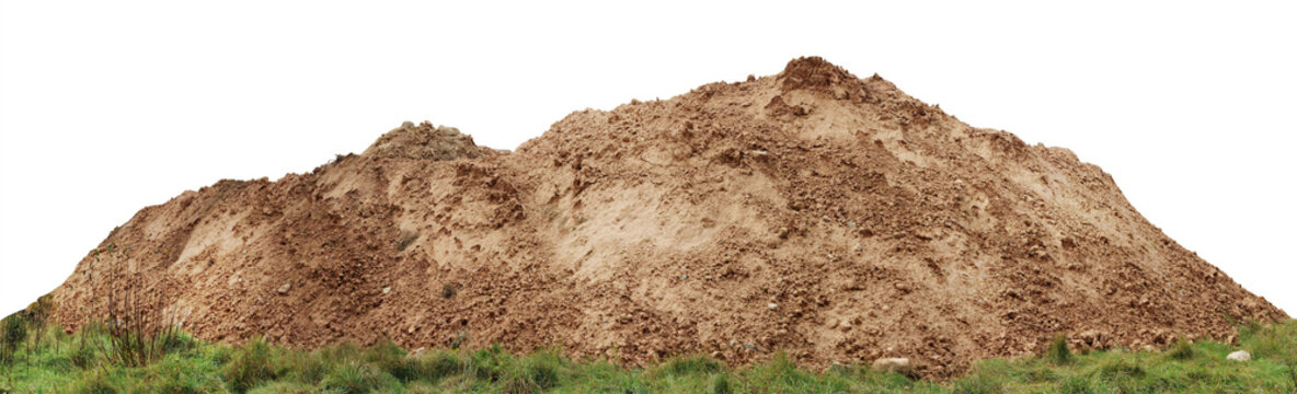 A large pile of construction sand  on forest grassy site.