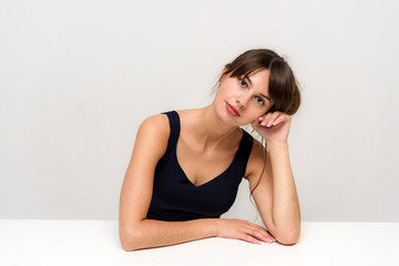 Studio photo portrait of a beautiful brunette girl on a white background sitting at the table.