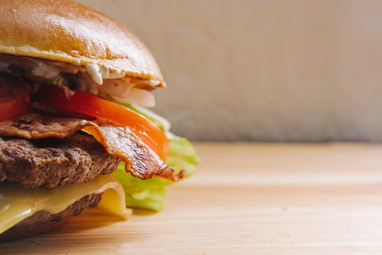 Delicious fresh homemade grilled burger on a wooden table with copyspace
