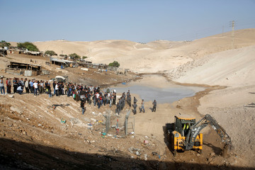 Activists protest in front of Israeli troops in the Palestinian Bedouin village of Khan al-Ahmar that Israel plans to demolish, in the occupied West Bank