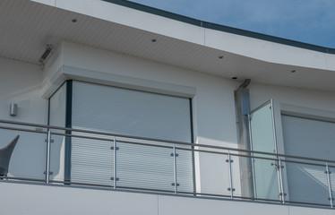 Fenster mit Rolladen und Balkonbrüstung