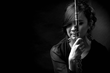 Fashion portrait in studio of beautiful young woman feeling happy with her flute against dark background in studio