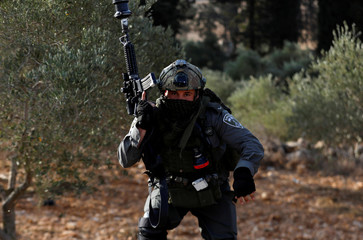 Israeli border policeman runs during clashes over an Israeli order to shut down a Palestinian school near Nablus in the occupied West Bank