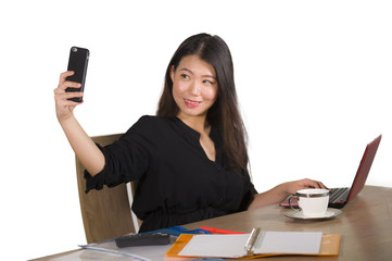 young beautiful and happy Asian Chinese business woman taking selfie photo with mobile phone at corporate company office desk smiling playful in female entrepreneur success