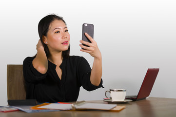 happy Asian Chinese business woman taking selfie photo with mobile phone at corporate company office desk smiling playful in female entrepreneur success