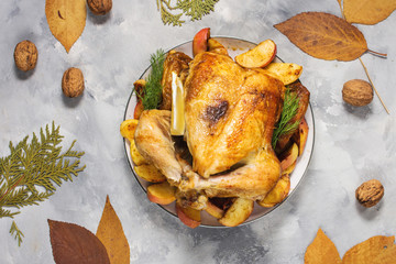 Roasted turkey with apples on a rustic concrete table decorated with walnut and autumn leaf. Flat lay.