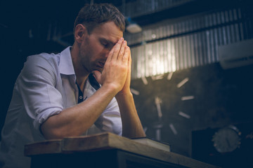 The young man handsome caucasian Americans handsome man sitting with hands clasped in prayer for blessings from God. A Bible rested on a wooden table with copy space.