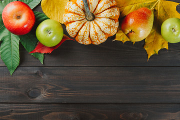 Pumpkin with colorful maple leaves, ripe apples and pear on dark wooden background. Autumn seasonal image with free space for your text