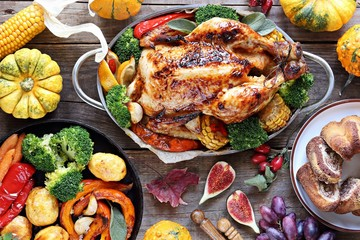 Thanksgiving day food. Festive family dinner table with roasted chicken or turkey and various of vegetables.