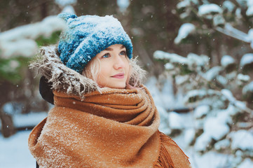 winter portrait of happy young woman walking in snowy forest in warm outfit, knitted hat and oversize scarf. Exploring nature on winter and Christmas vacations concept