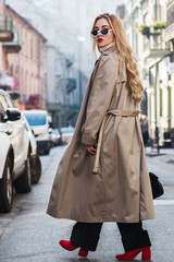 Outdoor full body fashion portrait of young beautiful fashionable woman wearing trendy beige long trench coat, stylish sunglasses, black trousers, red boots, model walking in street of european city