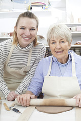 Portrait Of Senior Woman Rolling Out Clay With Teacher In Pottery Class