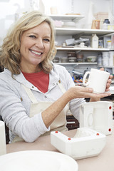 Portrait Of Mature Woman In Pottery Studio Casting Mug