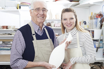 Portrait Of Senior Man With Teacher Looking At Vase In Pottery Class