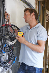 Electrician Fitting Wiring On Construction Site