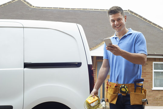 Portrait Of Electrician Checking Message On Mobile Phone