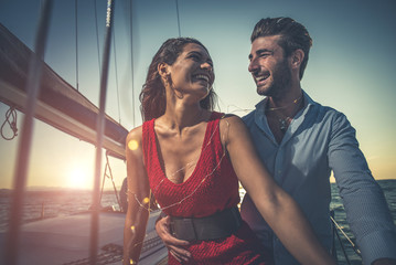 happy couple taking a romantic cruise on the sail boat Fototapete