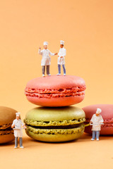 miniatures peoples : chefs in front of delicious macaroons