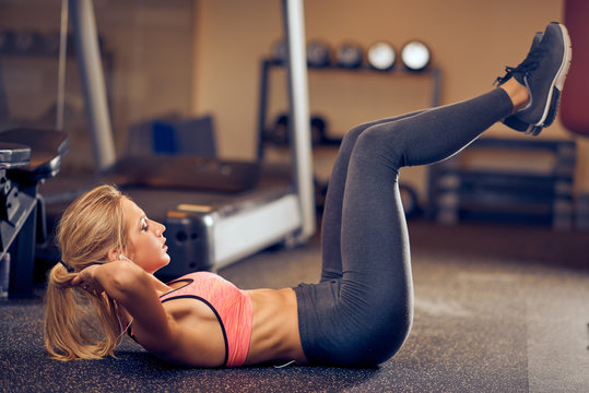 Sporty woman doing crunches with lifted legs. In background exercise equipment.