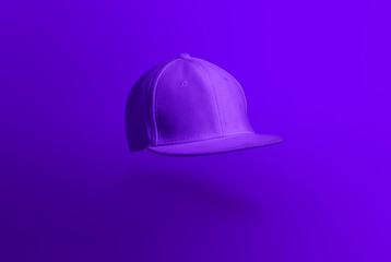 Blank cap in perspective view. Purple snapback on purple background. Blank baseball snap back cap for your design. Mock up hat cap for you logo, brand identity etc.
