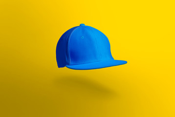 Blank cap in perspective view. Blue snapback on yellow background. Blank baseball snap back cap for your design. Mock up hat cap for you logo, brand identity etc.