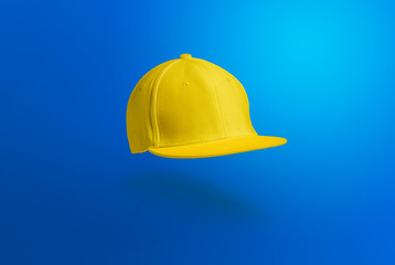 Blank cap in perspective view. Yellow  snapback on blue background. Blank baseball snap back cap for your design. Mock up hat cap for you logo, brand identity etc.