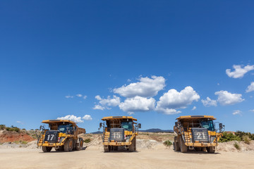 Three large dumper trucks in a row with copy space