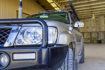 Extreme closeup of headlight and bull bar on four wheel drive vehicle