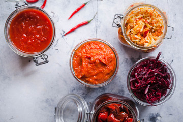Fermented preserved jars red cabbage, beetroot, tomato sauce, red peppers fried Canning food overhead
