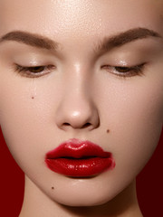 Cosmetics, makeup and trends. Bright lip gloss and lipstick on lips. Closeup of beautiful female mouth with red lip makeup. Beautiful part of female face. Perfect clean skin in red light