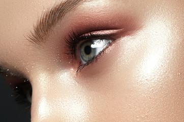 Close up view of blue woman eye with beautiful golden shades makeup. Classic make up. Perfect shape make-up and long lashes. Cosmetics and make-up. Closeup macro shot of fashion eyes visage
