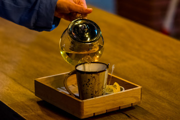 Woman pouring the tea in the cup
