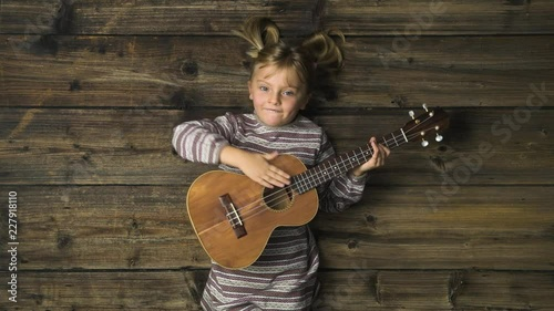 Overhead happy child girl on vintage wooden background
