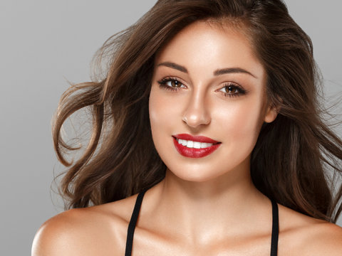 Beautiful brunette with red lips and long hair tanned skin with beauty eyes face closeup
