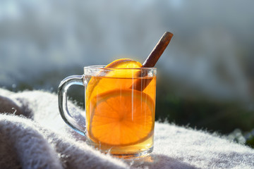 hot tea with orange slices and cinnamon on a wool blanket against a blurred gray blue background with copy space