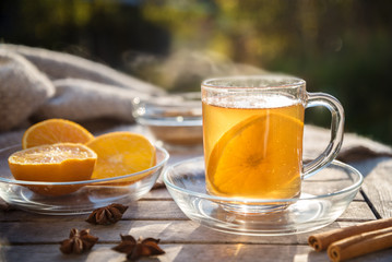 hot ginger tea with orange slices and spices on a wooden table in the sun, healthy drink against cold, copy space