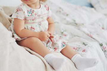 Childhood concept. baby girl in cute dress siting at bed playing with toys by the home. White vintage childroom