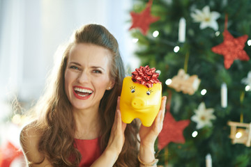 smiling young woman showing yellow piggy bank with red bow