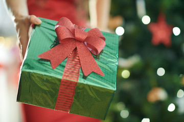 Christmas present box in a hand of woman near Christmas tree