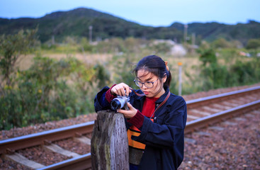 Young asian woman taking a picture in front of train tracks