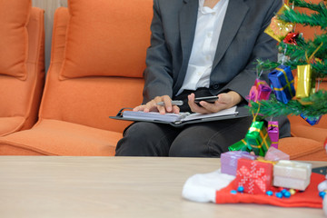 woman holidng notebook & smart phone with gift present boxes christmas tree on table. xmas new year celebration.