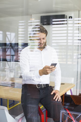 Happy young man using his smart phone at office