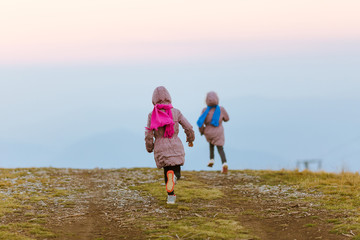 Two young girl running, beautiful dusk sky in the background, photographed from behind.