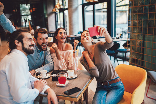 Group of Happy friends having making selfie in cafe