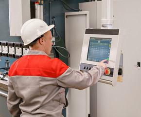 control computer display of Machine. Manufacture workers adjusts the machine in the warehouse. the production of ventilation and gutters. Tool and bending equipment for sheet metal.