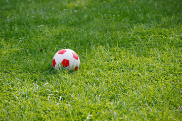 Red-white soccer ball on green grass. Football equipment.