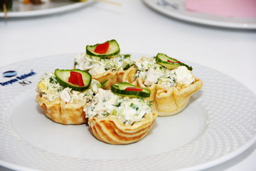 tartlets with salad and green cucumber on a white plate