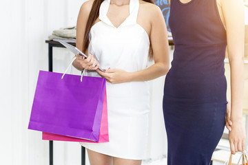 Young beautiful woman and friendships with shopping bags and tablet enjoying in shopping at clothing store.Lady choosing shopping online. Copy space.