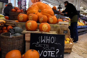 A shopkeeper arranges vegetables beside Halloween pumpkins in a shop with Ireland's Presidential candidates faces carved into them ahead of an upcoming Presidential election in Dublin